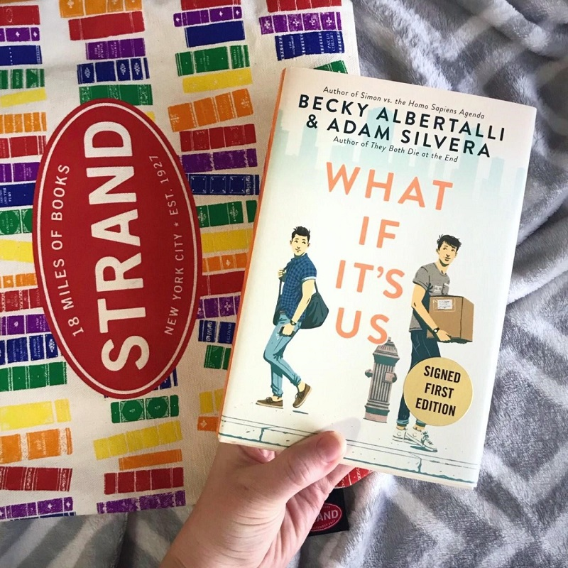 What If It's Us on a Strand Bookstore rainbow book spine tote with a gray and white blanket underneath