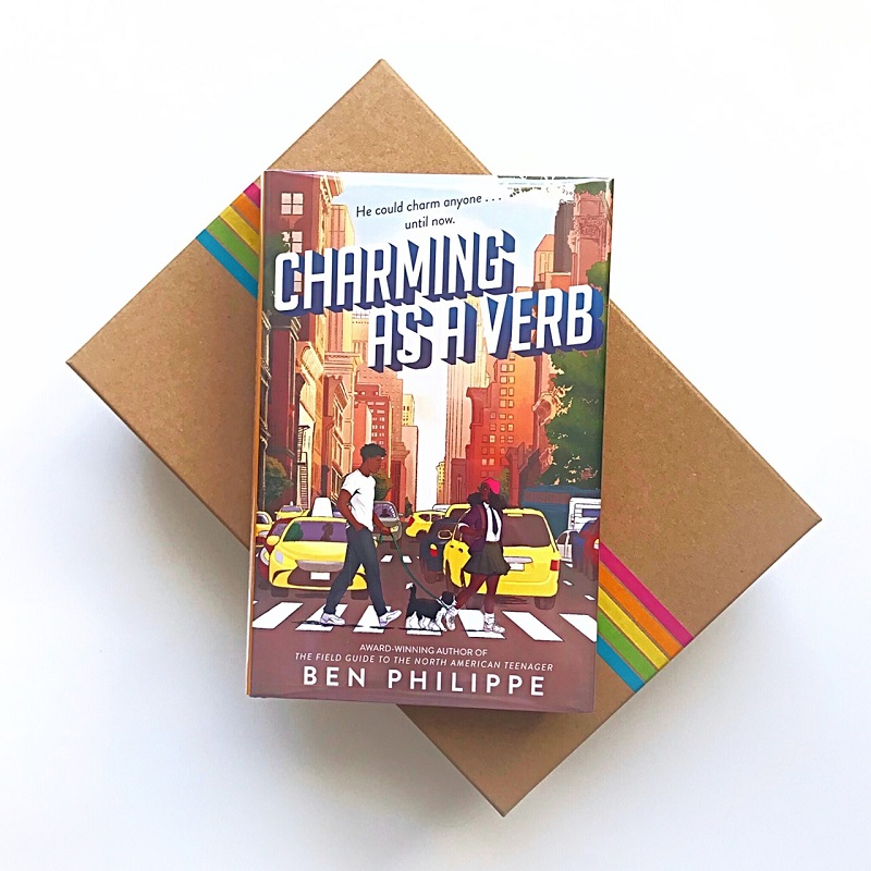 Charming As a Verb sits on a light brown photo box that has strands of multi-colored tape across the top. The book showcases the two main characters, Henri and Corinne, on the cover as they cross a busy New York City street in front of two yellow taxis. Both the book and the box are on a white background.