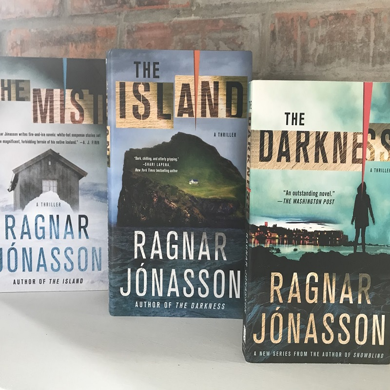 Three books: The Darkness, The Island, and The Mist by Ragnar Jonasson standing against a brick wall;