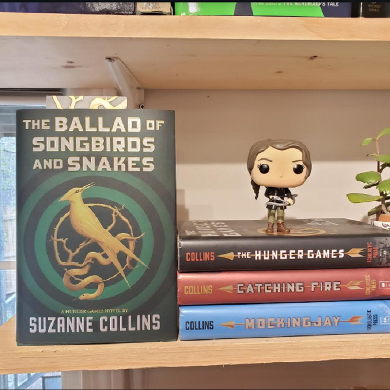 A copy of The Ballad of Songbirds and Snakes next to the original trilogy.