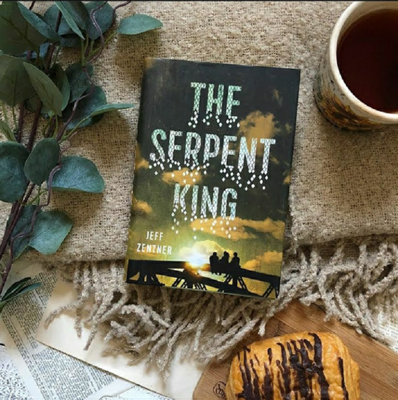 A copy of The Serpent King on a blanket next to a cup of coffee.