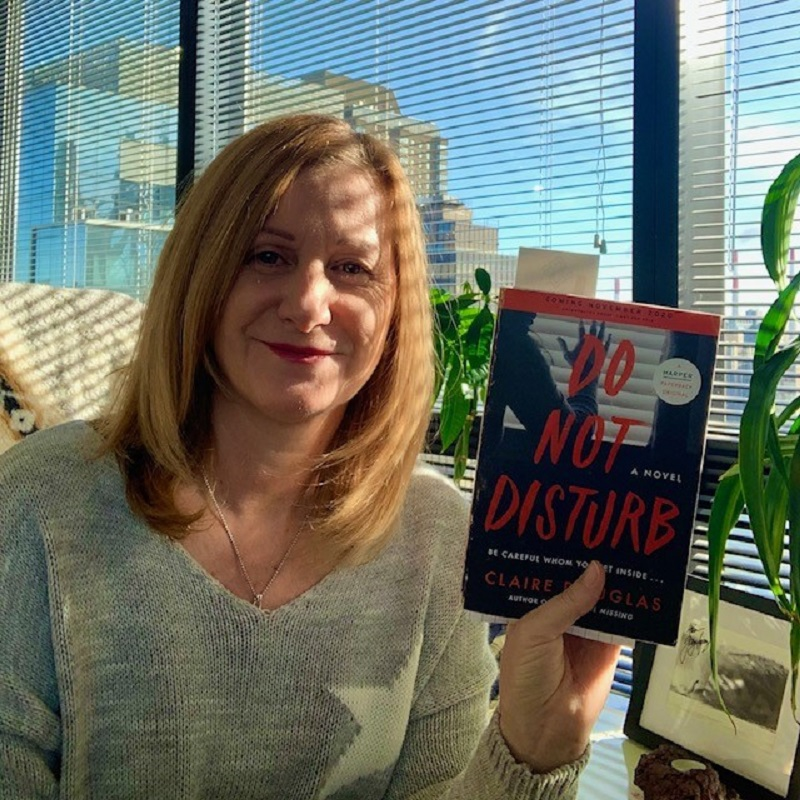 Our contributor, Jacqueline Hodges, sitting in the sunshine in New York City, in front of a potted plant and photograph, holding a copy of the book Do Not Disturb by Claire Douglas.