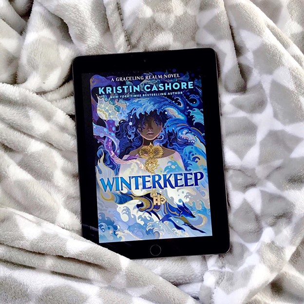 The Winterkeep cover is shown on a tablet screen, which rests on a gray and white blanket. I
