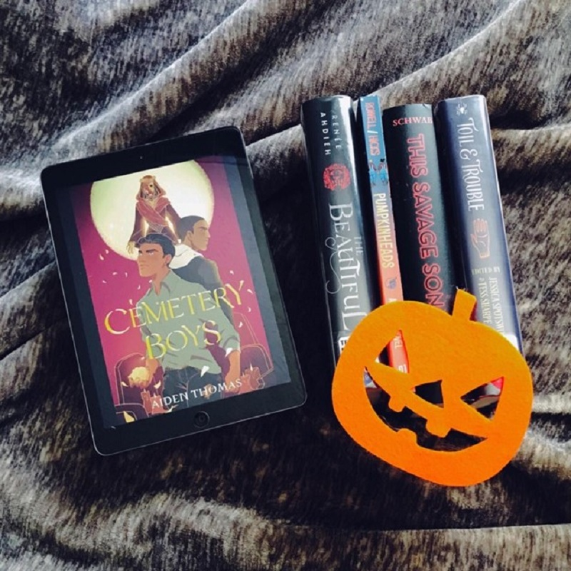 On a gray-brown blanket, the cover of Cemetery Boys is on a tablet screen, to the left of the four other books, The Beautiful, Pumpkinheads, This Savage Song, and Toil & Trouble. An orange felt jack-o'-lantern sits on the bottom of the spines of the four books.
