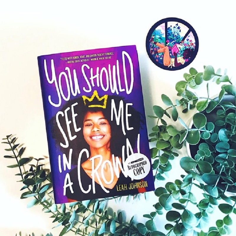 You Should See Me in a Crown is on a white background with a small coaster with a Black girl reading a book sitting nearby. A plant's long, hanging stems curl around and underneath the book.