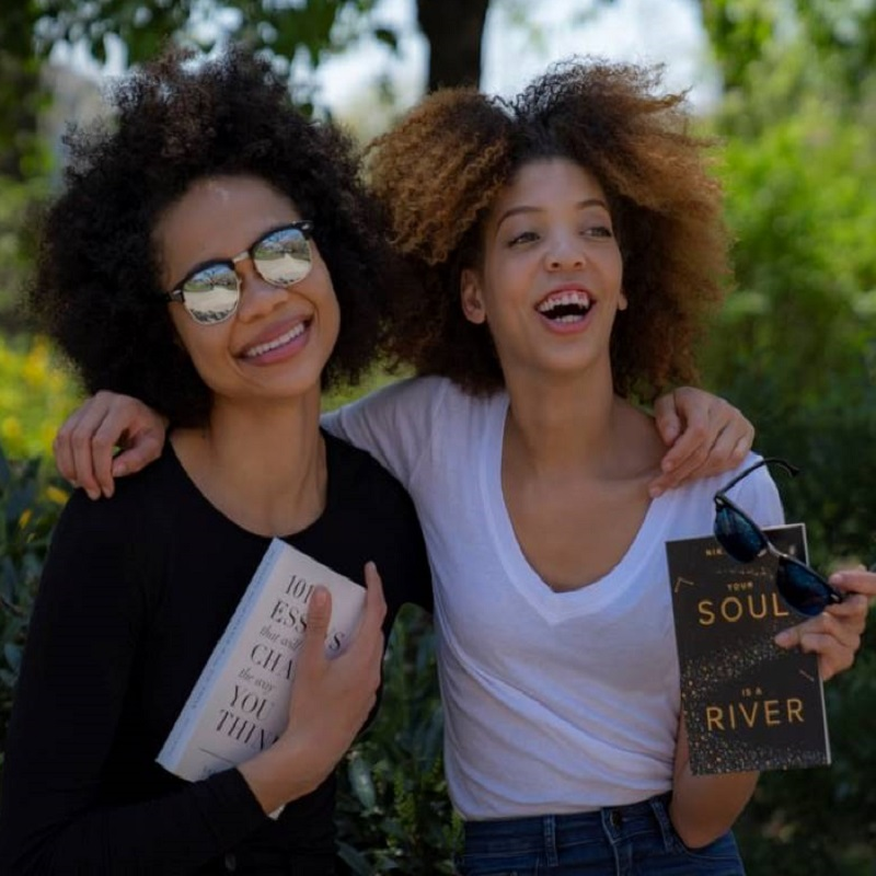 """one woman and one girl standing with arms around each other smiling and holding books"""" - What Makes a Good Book Club Book?"""