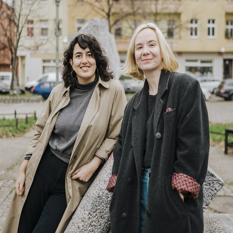 Authors Onjuli Datta (left) and Mikaella Clements (right) stand in front of a cream and tan coloured building and leafless trees. Off to the left is a red coloured building. There are patches of grass and parked cars behind them.
