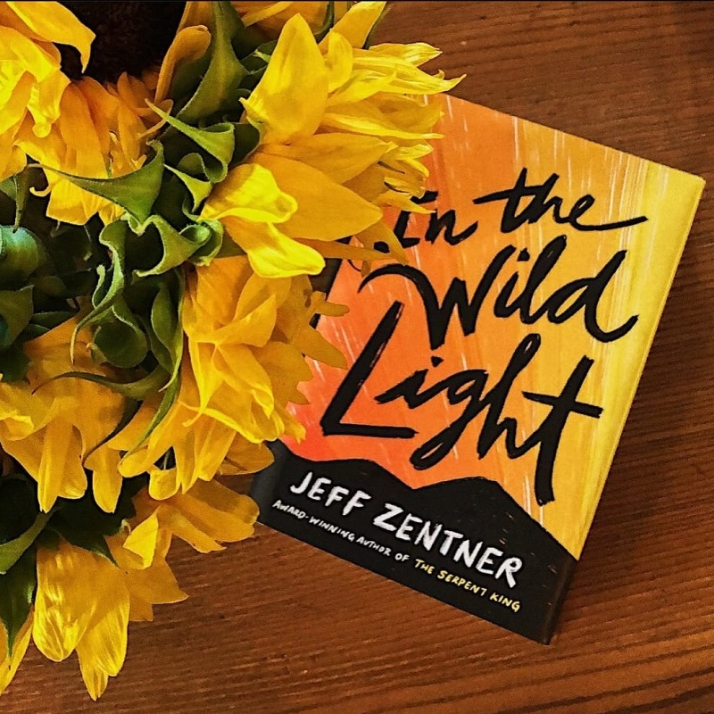A copy of In the Wild Light next to a bouquet of yellow flowers on a brown wooden table.