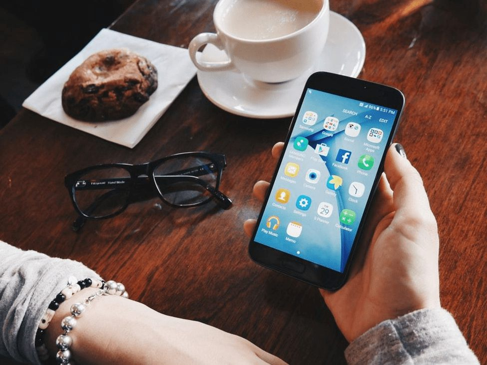 A person sitting at a table holds a cell phone in their hands with glasses, coffee, and a cookie