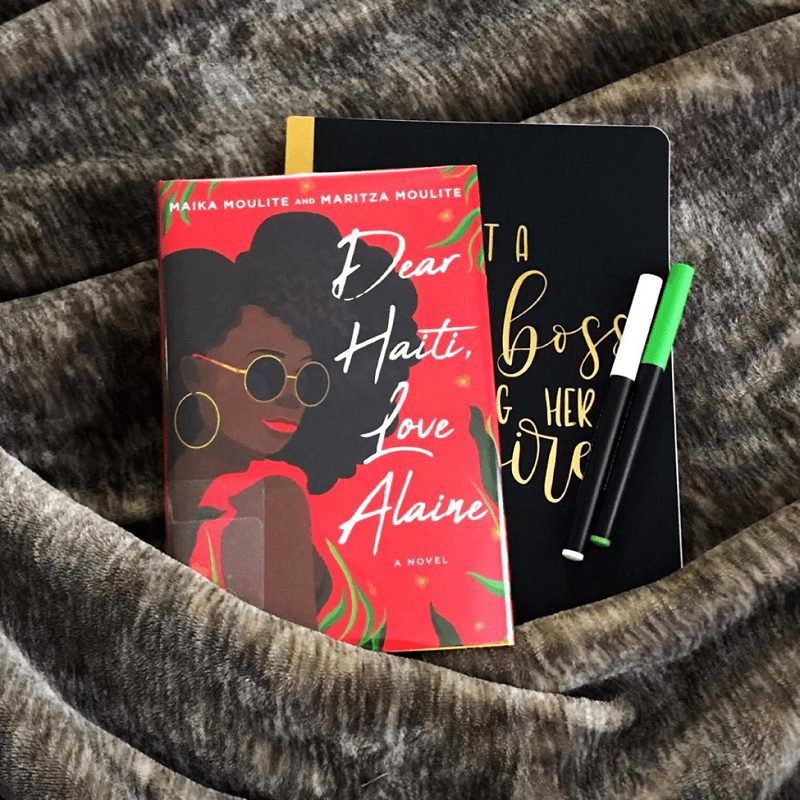 Dear Haiti, Love Alaine rests on a black and gold notebook next to two markers. A brown and tan blanket is underneath, but drapes across the bottom corners of the book and notebook.