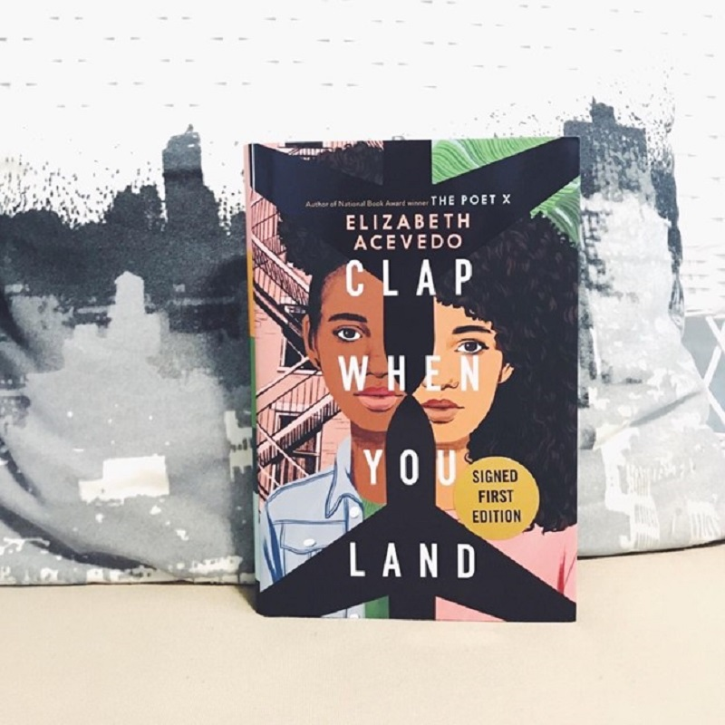 Clap When You Land leans against a pillow with a black and gray skyline on it. The cover shows two teenage girls separated by the black outline of airplanes pointed at one another.