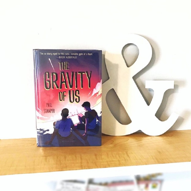 The Gravity of Us, with its pink and navy cover, sits on a pine shelf next to a white ampersand.