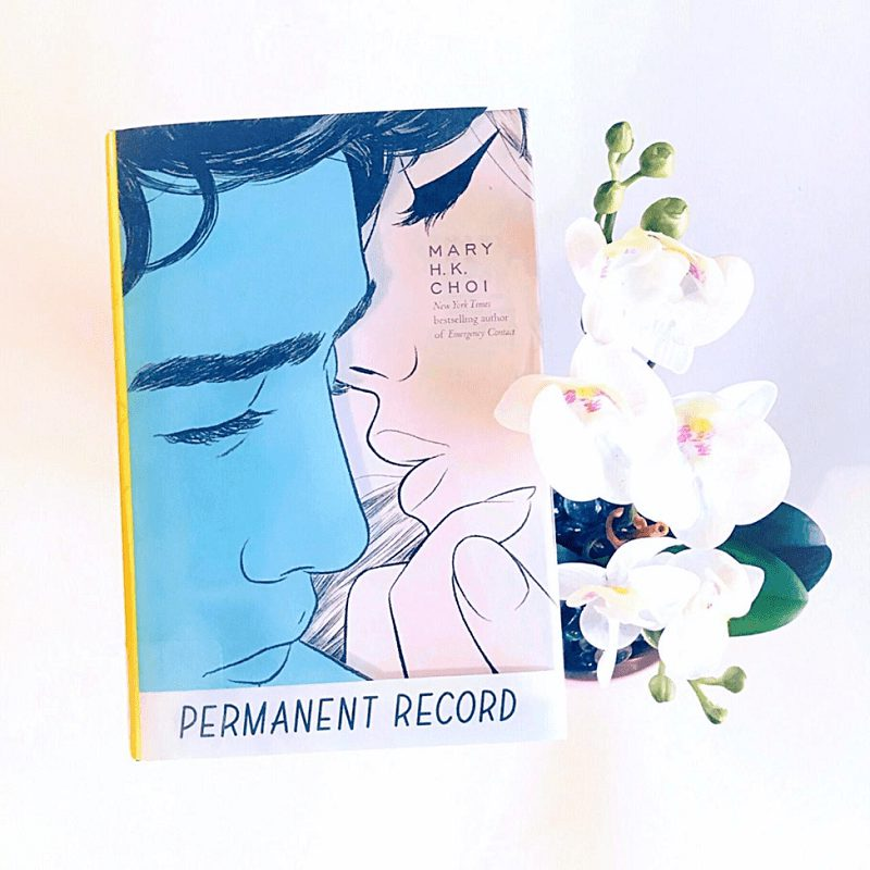 A potted white orchid sits near a raised copy of Permanent Record
