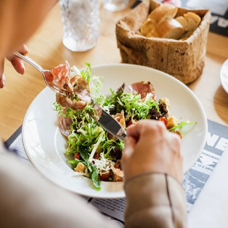 on a table is a bowl of salad sitting on top of a black and white placemat. A person is holding a fork in their left hand and a knife in their right hand, about to eat the salad. In front of the bowl sits a basket of bread and a glass of water. (image via unsplash.com)
