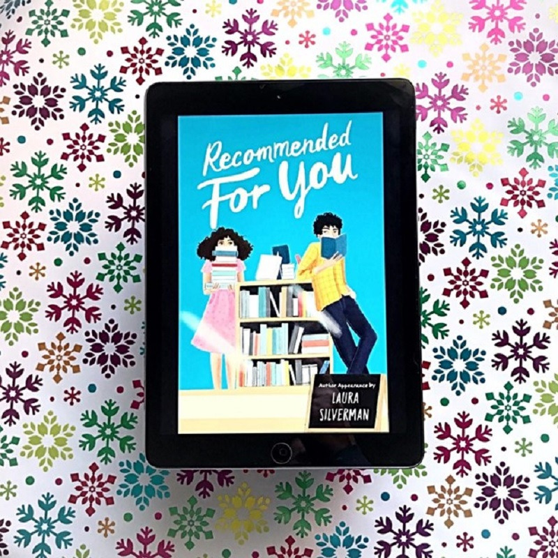 The blue cover of Recommended for You is shown on an iPad screen, which rests on a colourful snowflake-covered background.