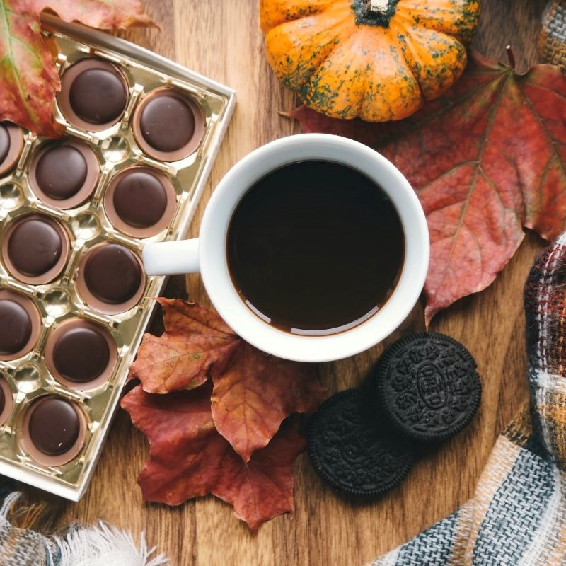 """A mug of coffee sitting on a plank board surrounded by fall leaves, Oreo cookies, a box of chocolates and a blanket."""" Feeling Good About Fall: 10 Activities for Self-Care"""