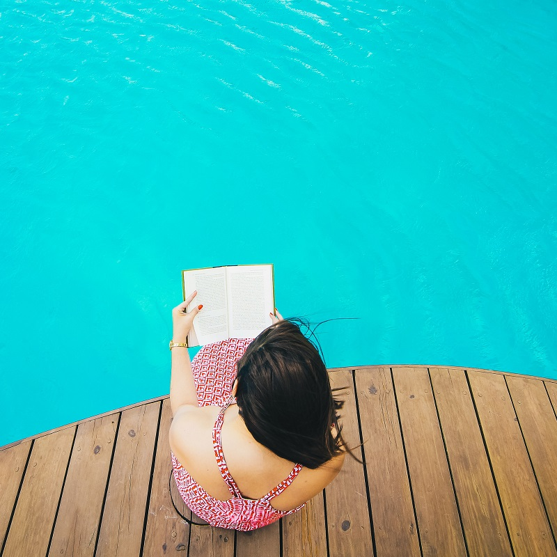 Woman sitting on the dock reading – Suspenseful Sizzlers for Summer 2021