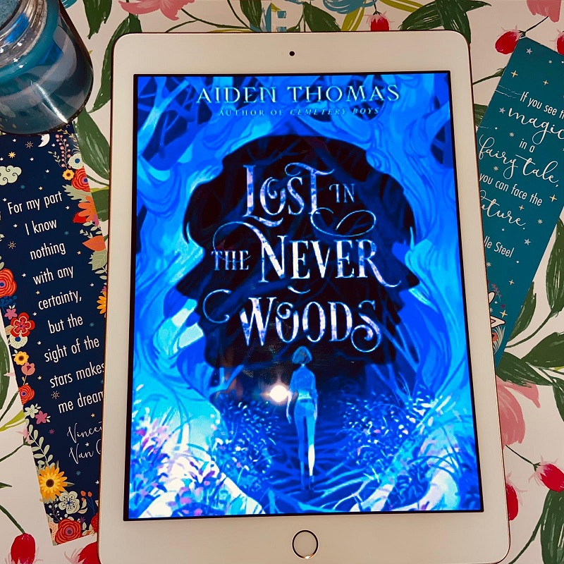 A picture of Lost in the Neverwoods on an Ipad sits in the centre of a floral background, with a bookmark, slightly angled to the left and right, and a blue candle in the top left corner.