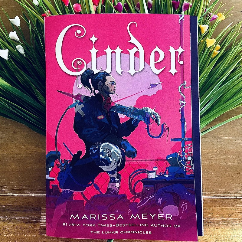 A picture of Cinder book cover and multicoloured flowers