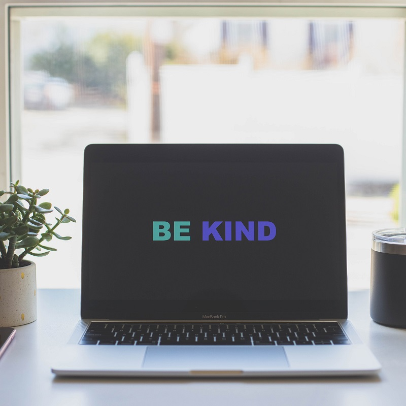 a laptop sits in the middle of a desk in front of a window. To the left is a small succulent plant in a white vase, to the right is a travel mug. On the computer screen are the words be kind.