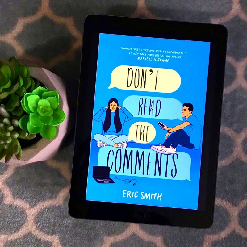 The cover of Don't Read the Comments on a tablet, next to a green succulent on a blue blanket.