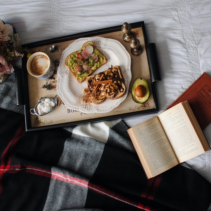 a tray of breakfast items including avocado toast and other fancy toasts laying on top of white sheets and a blanket with a bouquet of flowers to the left and some books on the right - top five books for book club discussion