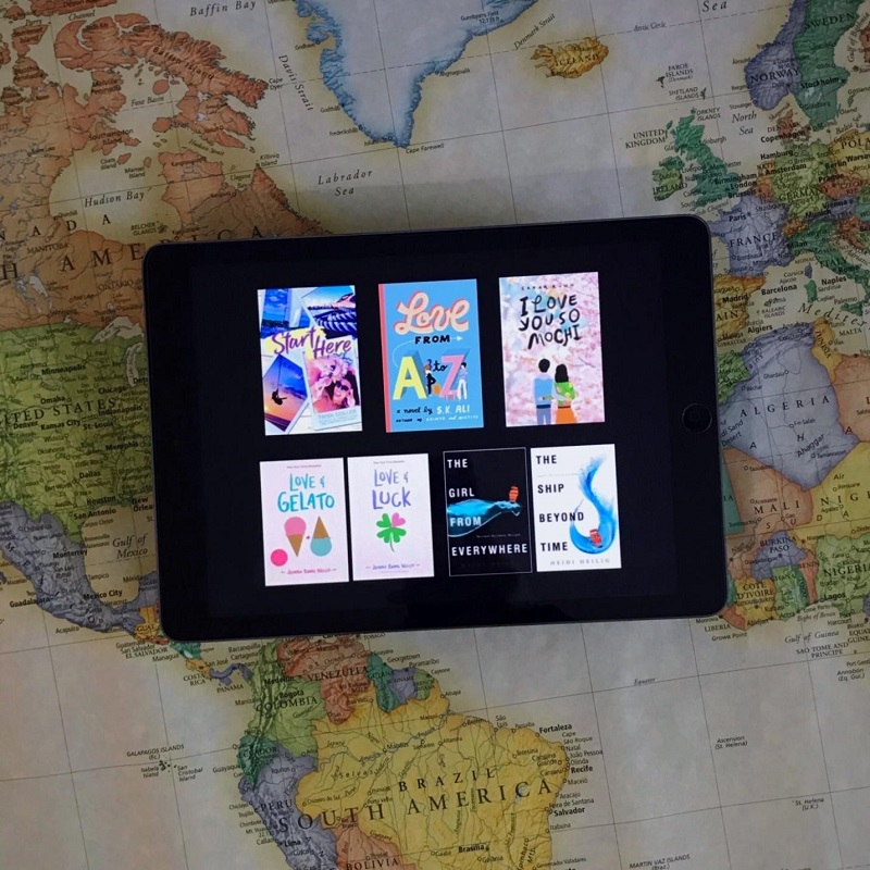 The digital covers of all seven books featured are shown on a tablet, which lies on a colourful world map. YA books that take you places