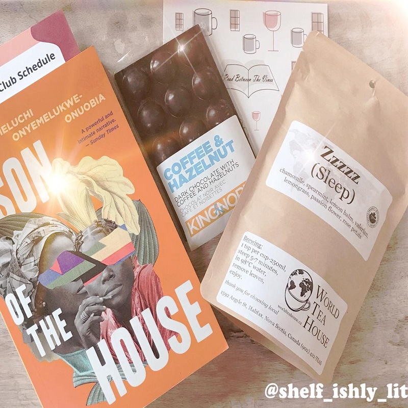 Book on the left lays beside chocolate and a bag of tea with a notecard on a pale wood background;