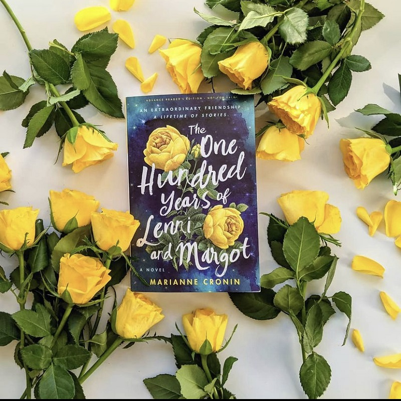 : the book The One Hundred Years of Lenni and Margo laying amongst a bed of yellow roses on a white surface