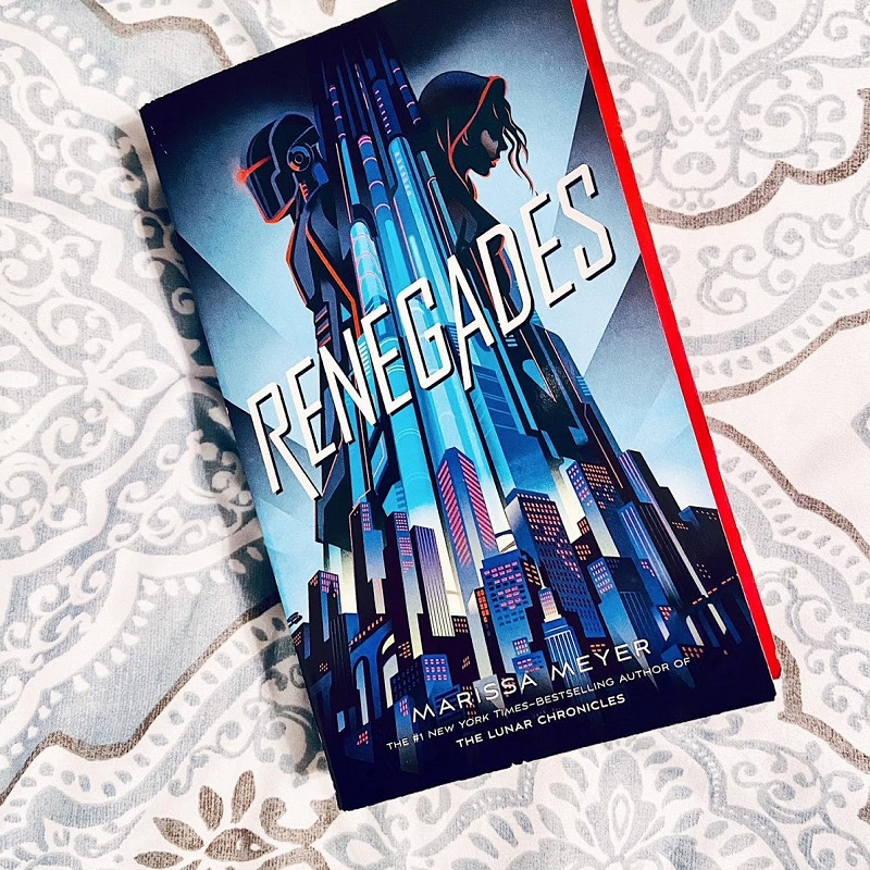A copy of Renegades by Marissa Meyer sits on a white blanket with a brown and grey floral design.
