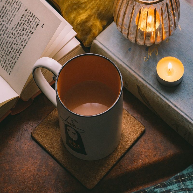 Cozy setting for reading 5 spooky books that might give you a fright. Table set with a coffee mug, open book, and lit candle.