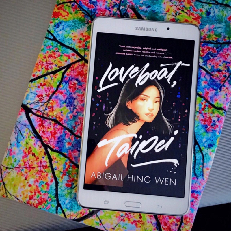 The cover of Loveboat, Taipei shown on a white tablet resting a book sleeve with tree branches and colourful leaves.