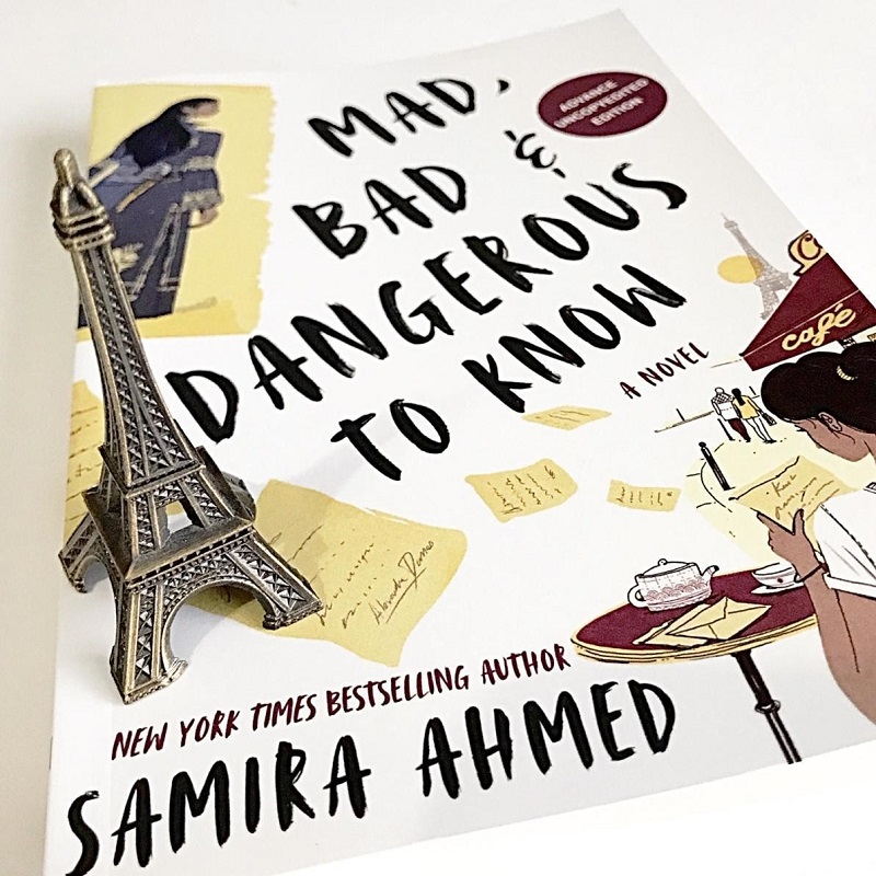 A miniature Eiffel Tower sits on a copy of Mad, Bad & Dangerous to Know by Samira Ahmed.