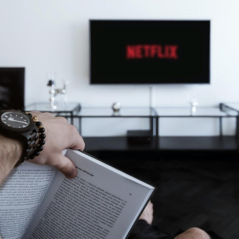 A person holding a book open in a minimalist living room with the Netflix logo on the TV in the background. Ready to watch a book to movie adaptation