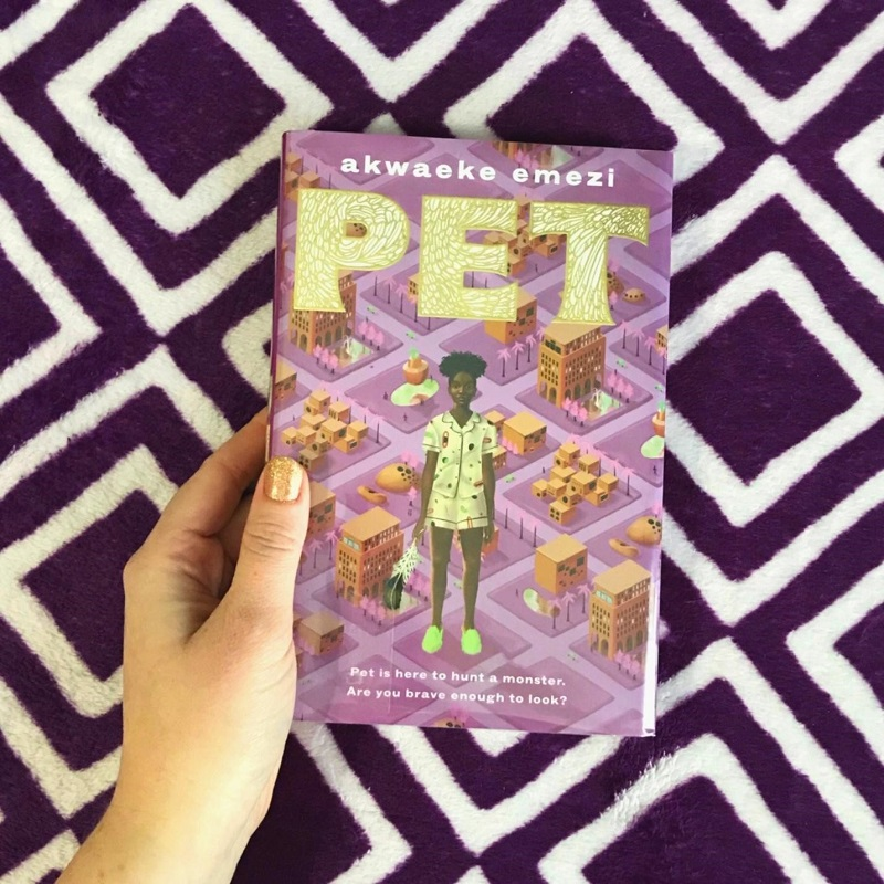 A copy of the lavender and gold Pet is held over a dark purple and white patterned blanket by a hand with the fingernails painted gold.