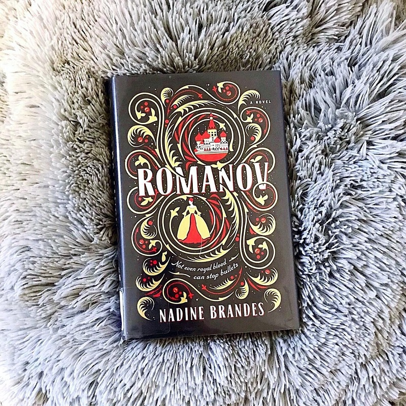 A copy of Romanov rests on a shaggy, gray pillow which seems to fan out around it. I