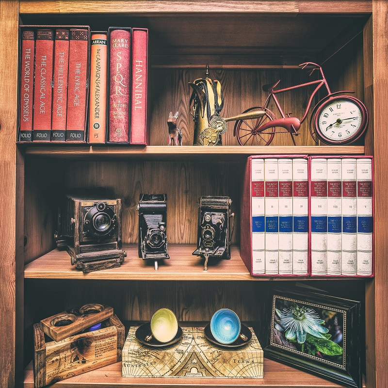 """Books on a bookshelf with a picture frame and various objects"""