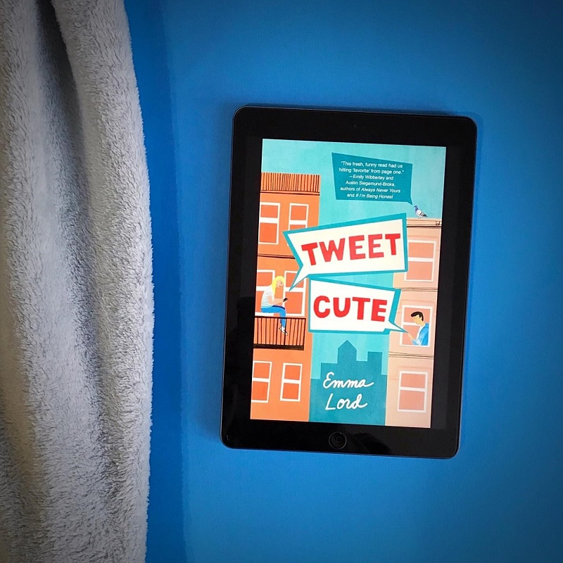 The cover of Tweet Cute on a tablet screen near a light blue blanket on a bright blue background.