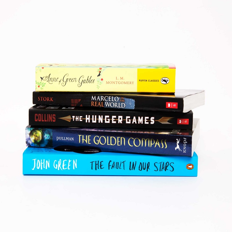 Photo of a stack of Young Adult books. (Top to bottom): Anne of Green Gables by L. M. Montgomery, Marcelo in the Real World by Francisco X. Stork, The Hunger Games by Suzanne Collins, The Golden Compass by Philip Pullman and The Fault in Our Stars by John Green.